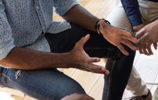 Black people in a circle, focus on hands