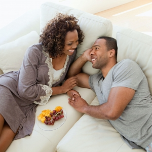 African American couple smiling, looking at each other, lying on couch